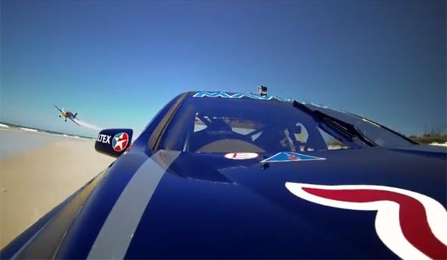 V8 Supercar on Sand Races Red Bull Stunt Plane