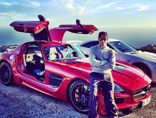 Lewis hamilton poses with his red sls amg black and sl 65 for Mercedes benz f1 drivers